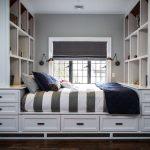 Кровать возле окна с встроенными стеллажами и ящиками для хранения
