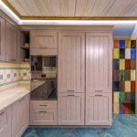 Интересное оформление кухни с высокими шкафчиками и пеналами в стиле кантри