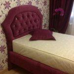 Односпальная кровать с бордовым изголовьем капитоне