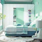 Шкаф, кровать и столик в интерьере спальни в зеленом цвете
