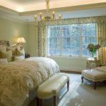 Традиционная спальня с высокой мягкой кроватью и необычным креслом с пуфиками