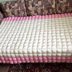 Бело-розовое одеяло бонбон на большой диван