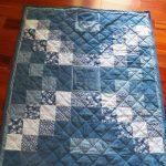 Красивое лоскутное одеяло с симметричным рисунком из старых джинсов