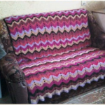Плед на диван из остатков пряжи, связанный разноцветными зигзагообразными полосками