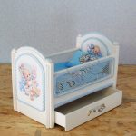 Самодельная кроватка с сетчатыми бортиками и голубым постельным