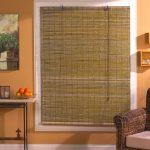 Бамбуковая штора рулонного типа на окне жилой комнаты