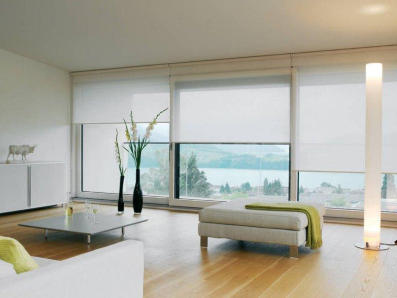 Декорирование панорамного окна гостиной рулонными шторами