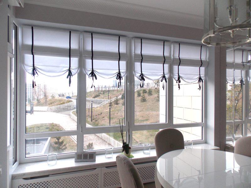 Белые римские шторы бескаркасного типа на пластиковом окне кухни