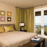 Бледные желто-зеленые шторы используются в спальне с песочными обоями