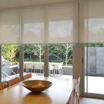 Солнцезащитные рулонные шторы на большом окне кухни-гостиной