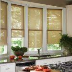 Открытые рулонные шторы на створках кухонного окна