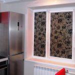 Современный холодильник около окна кухни