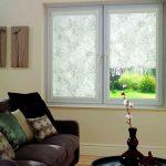 Диван перед окном с полупрозрачными шторами