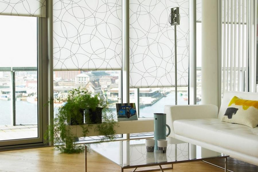 Панорамные окна гостиной с рулонными шторами из легкой ткани