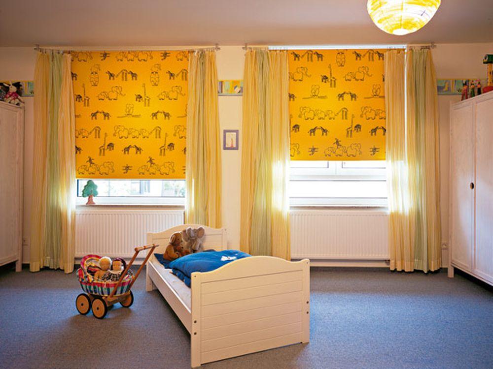 Желтые шторы с черным принтом на окнах детской комнаты