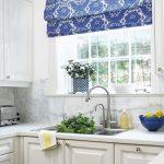 Рулонная бело-синяя штора отлично смотрится на кухонном окне