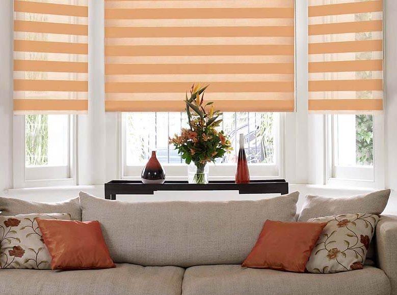 Серый диван около окна с рулонными шторами