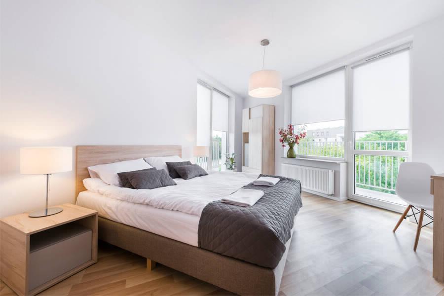 Белые шторы с электромотором на окне с балконом