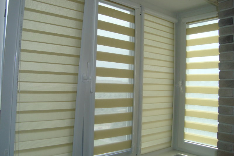 Рулонные шторы типа день-ночь с направляющими на окнах балкона
