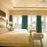 Светло-бежевая комната и яркие изумрудные шторы отличное сочетание для спальни
