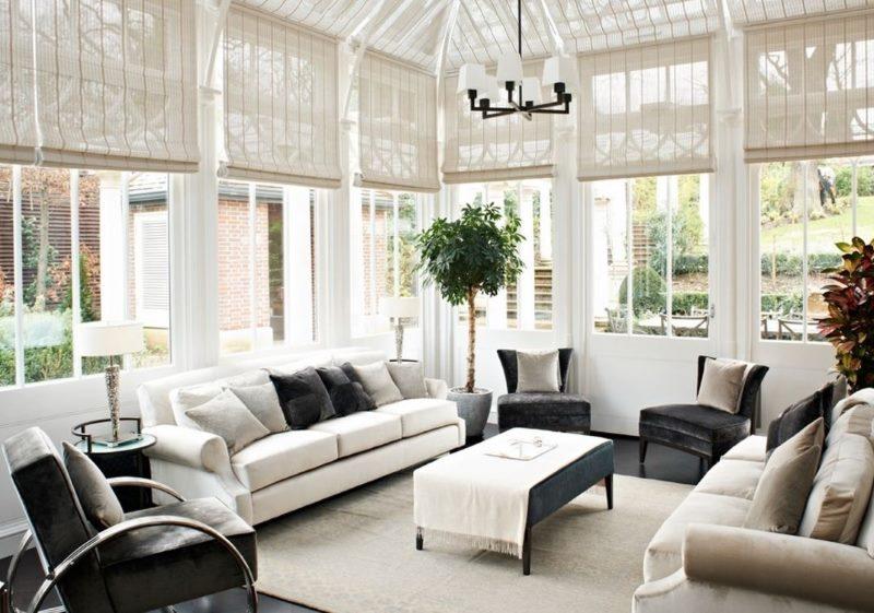 Интерьер белой гостиной с рулонными шторами из бамбука