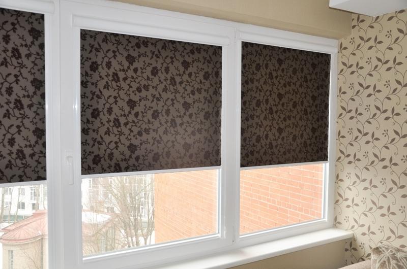 Темные шторы рулонного типа на пластиковом окне лоджии