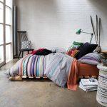 Высокий матрас для сна на полу положен на каркас для более удобной эксплуатации