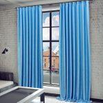 Яркие голубые шторы отлично смотрятся в гостиной в стиле лофт