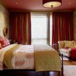 Зелено-бордовые шторы в интерьере оригинальной спальни