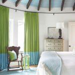 Зелено-голубые шторы в интерьере спальной комнаты