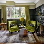 Зеленые кресла ,абажур и шторы разбавляют гостиную в черном цвете