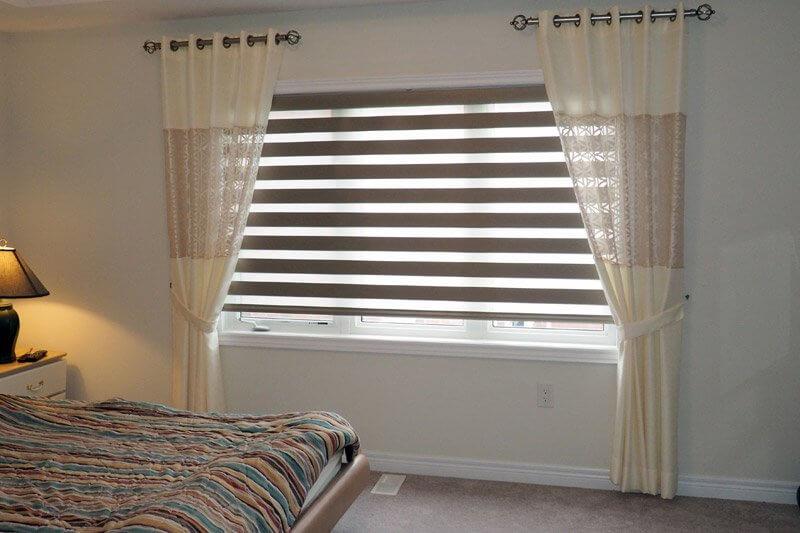 Сочетание штор зебра с прямыми шторами на окне спальни