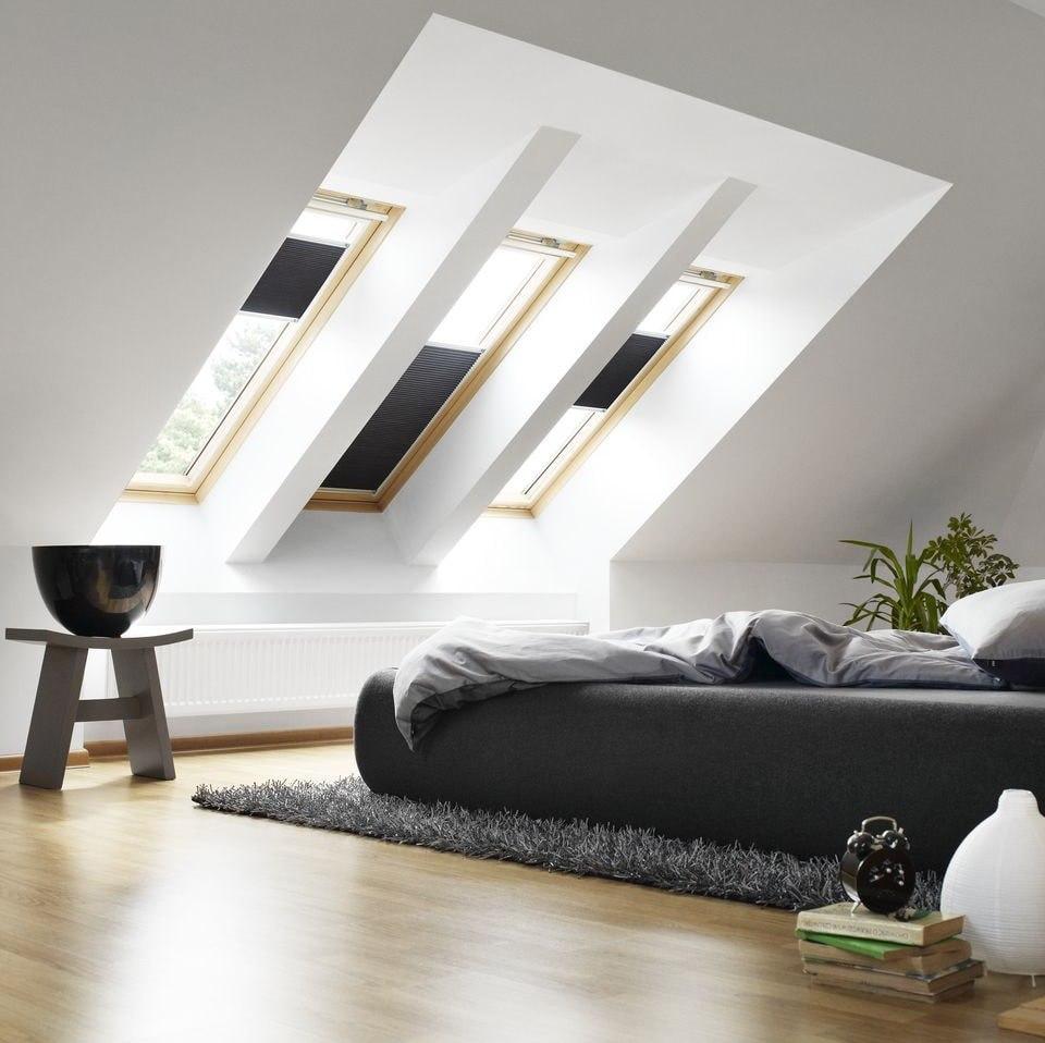 Черная кровать в белой комнате мансарды