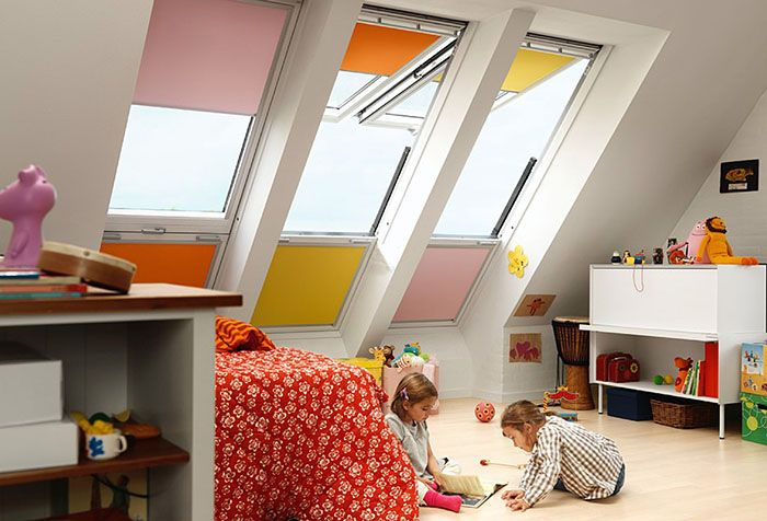 Разноцветные рулонные шторы на окнах детской в мансарде