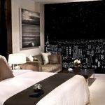 Просторная спальня с роллетой ночной город на окне