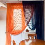 Сочетание гардин различного цвета на окне жилой комнаты