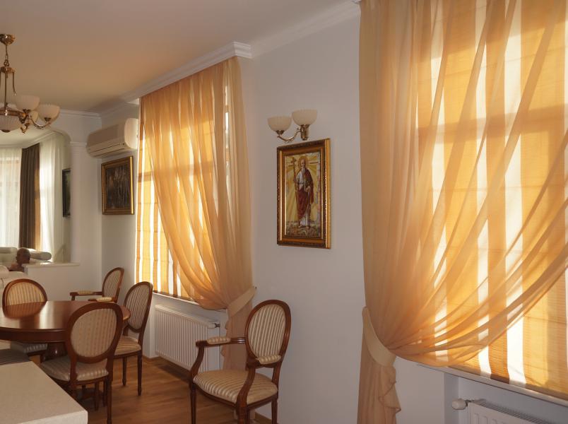 Светло-коричневый тюль на окнах классической гостиной