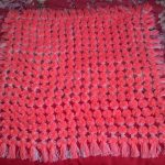 Плед из помпонов кораллового цвета