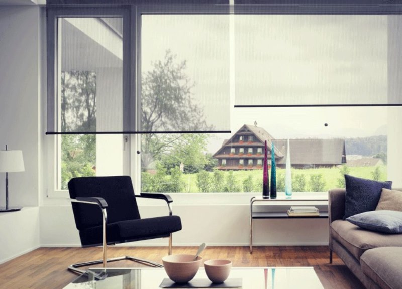 Прозрачные рулонные шторы на большом окне гостиной
