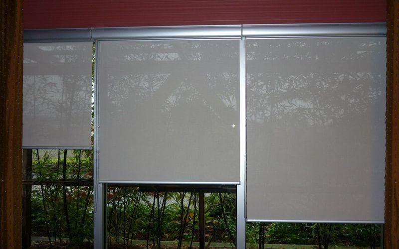 Солнцезащитные роллеты на окне застекленного балкона