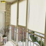 Светлые роллеты на панорамных окнах балкона