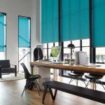 Голубые шторы рулонного типа на высоких окнах