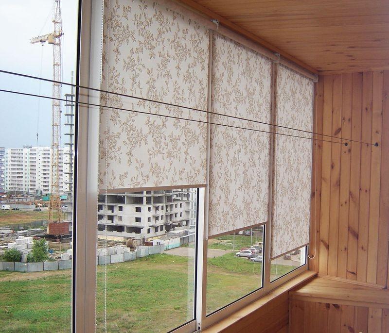 Светлые рулонные шторы на раздвижных створках балконного окна