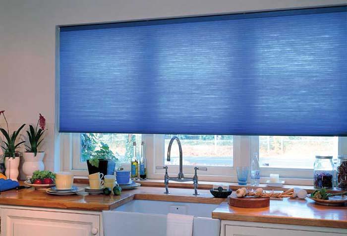 Синяя рулонная штора в проеме кухонного окна