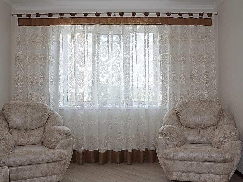 Два кресла перед окном с тюлем