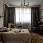 Черный комод напротив кровати в спальне