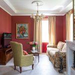 Пестрый диван в гостиной с бардовыми стенами