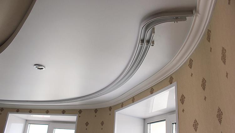 Гибкий карниз на потолке комнаты с эркером