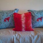 Голубые подушки с красными котятами и красной подушкой в середине