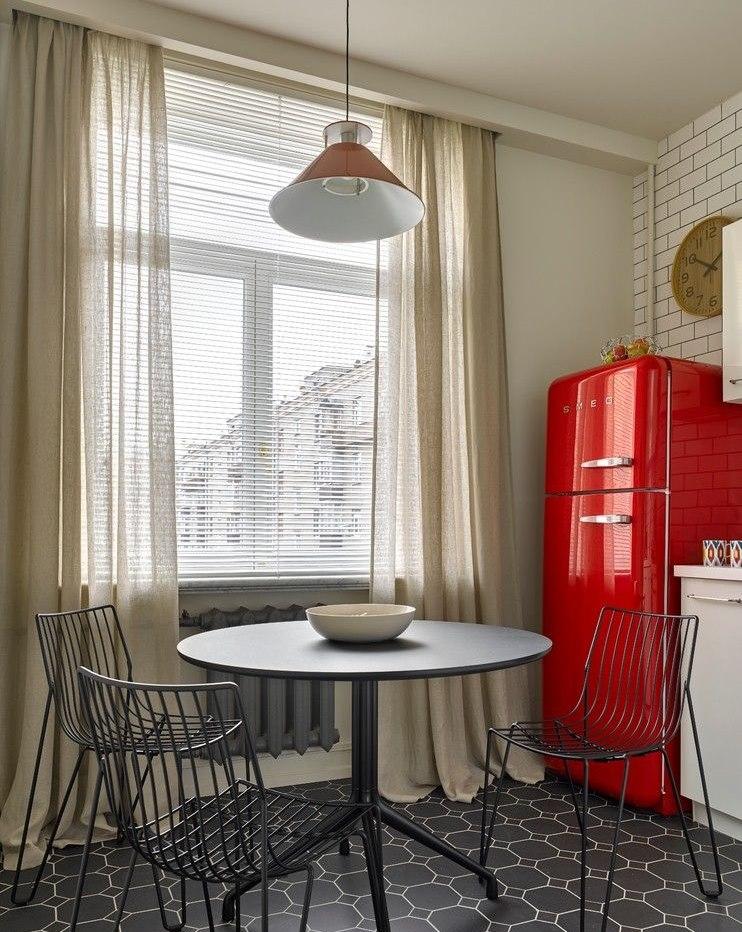 Красный холодильник около окна кухни с легкими шторами